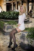 foto of posh  - Elegant pretty blonde young woman sitting in white dress in posh city setting in Europe - JPG