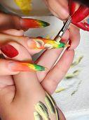 stock photo of fingernail  - Master draws design floral on female fingernails. ** Note: Soft Focus at 100%, best at smaller sizes - JPG