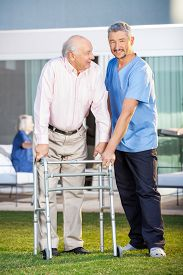 foto of zimmer frame  - Portrait of smiling caretaker assisting senior man to use walking frame at nursing home lawn - JPG