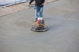 stock photo of wet  - Construction worker produces the grout and finish wet concrete with a special tool. Float blades. For smoothing and polishing concrete, concrete floors ** Note: Shallow depth of field - JPG