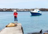 foto of sea lion  - Female sea lion relaxing close to a boy at coast of South Plaza island Galapagos - JPG