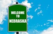 stock photo of nebraska  - Green road sign with greeting message Welcome to NEBRASKA isolated over clear blue sky background with available copy space - JPG