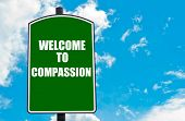 picture of compassion  - Green road sign with greeting message Welcome to COMPASSION isolated over clear blue sky background with available copy space - JPG