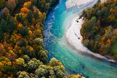 stock photo of unique landscape  - Pristine alpine turquoise river meandering through forested landscape in a sunny autumn day aerial view - JPG