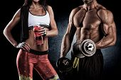 stock photo of pectorals  - Athletic man and woman with a dumbells - JPG