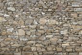 stock photo of tan lines  - Front view of a wall made up of irregular stones - JPG