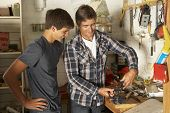 foto of workbench  - Father Teaching Son To Use Workbench In Garage - JPG