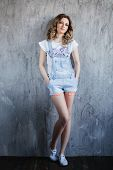 picture of denim jeans  - beautiful girl with curly hair in denim overalls beautiful girl with curly hair in denim overalls - JPG
