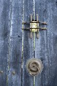 stock photo of peep hole  - Old wooden door with metal grid peephole and hinge in sunny day - JPG