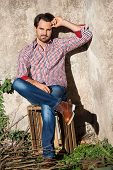 foto of wooden crate  - Smiling male model sitting on wooden crate with legs crossed - JPG