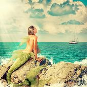 foto of fairy tail  - Beautiful Mermaid with fish tail sitting on rocks and looks at a ship on the horizon - JPG