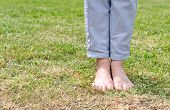 picture of barefoot  - Barefoot young woman standing on green grass and enjoy the touch of nature - JPG