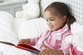 picture of pajamas  - Young Girl Wearing Pajamas In Bed Reading Book - JPG