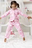 foto of pajamas  - Young Girl Wearing Pajamas Jumping On Bed - JPG