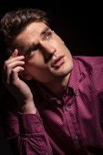 image of forehead  - Pensive young man looking up while holding his hand to the forehead - JPG