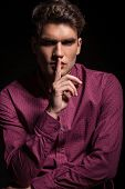 stock photo of silence  - Attractive young casual man making the silence gesture while looking at the camera - JPG
