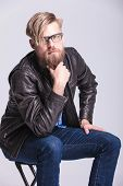 stock photo of long beard  - Blond casual man sitting on a chair while petting his long beard - JPG