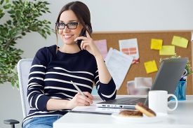 foto of adults only  - Portrait of confident young woman working in her office with mobile phone - JPG