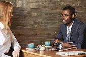 Постер, плакат: Young African Entrepreneur In Round Glasses Sitting At Business Lunch In A Caf& 233 And Drinking Co