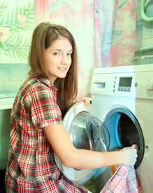 pic of washing machine  - Teenager girl doing laundry at her home - JPG