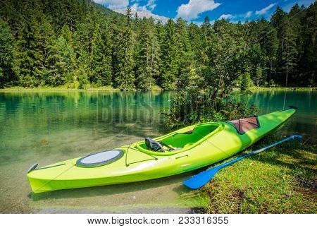poster of Scenic Kayak Trip. Green Single Kayak On The Shore Of Scenic Alpine Lake.