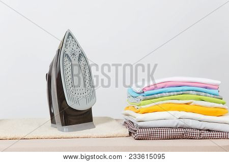 poster of Close Up Steam Iron, Ironing Colorful Clothes, Washed Laundry, Family Clothing On Ironing Board Isol