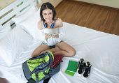 Cheerful Female Checking Money Cash And Packing Suitcase And Getting Ready For Traveling.bedroom Ful poster