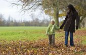 picture of mother daughter  - A young mixed race girl walking through the autumn leaves with her black mother - JPG