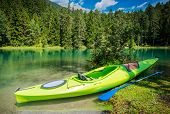 Scenic Kayak Trip. Green Single Kayak On The Shore Of Scenic Alpine Lake. poster