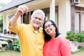 Portrait of a happy senior man posing with his wife while holding the keys of a residential house  poster