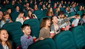 Close Sideview Of Funny Children Watching Fancy Movie, Sitting On The Comfortable Cinema Places. Kid poster