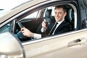 Formal Wearing Young Man Behind The Wheel. He Is Looking At Camera, Showing The Car Key And Smiling. poster