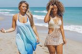 Confident multiethnic women in beachwear strolling on seaside relaxing in sunlight and speaking calm poster