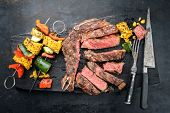 Barbecue dry aged wagyu cutlet with vegetable skewer as top view on a burnt cutting board  poster