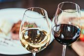 Close-up View Of Two Glasses With Red And White Wine On Table In Restaurant poster