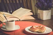 A Cup Of Coffee And A Plate With Baking. Books On The Shelf, Books On The Table. A Pot Of Flowers On poster
