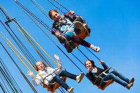stock photo of amusement park rides  - Teens on the chain swing carousel - JPG