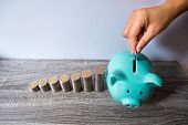 Woman Hand Putting Coin Into Blue Piggy Bank With Coins Growth Bar Graph, Step Up Growing Business T poster