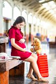 Asian Woman Pregnant Red Dress Sitting On A Bench At Carrying Red Luggage And Teddy Bear At Railway  poster