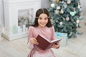 Must Read For Christmas Season. Happy Small Child Read Book By Xmas Tree. Adorable Little Girl Read  poster