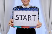 Woman Holding Notepad With Hand Written Start Word. Start Of Business, New Year, Relationship, Study poster