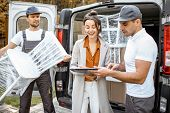 Delivery Company Employees Unloading Goods From A Car Trunk, Delivering Goods To A Womans Home. Happ poster