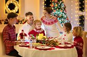 Family With Kids Having Christmas Dinner At Tree poster