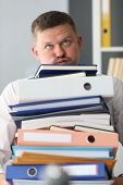 Portrait Of Tired Manager Holding Heavy Stack Of Document Folders. Accountant Preparing Important Bu poster