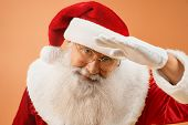 Happy Grandfather Santa Claus Wearing Red Traditional Costume, White Gloves And Eyeglasses Posing In poster
