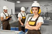 Beautiful Female Engineer Looking At Camera And Posing During Working Day On Metal Factory. Young Wo poster