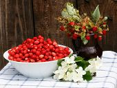 Wild Strawberry Bunch With Leaves On Wood Background. Strawberry Plant & Green Leaf In Summer Day. R poster
