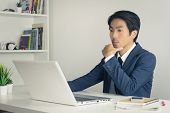 Asian Financial Advisor Or Asian Consulting Businessman In Suit Thinking In Front Of Laptop Monitor  poster