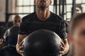 Closeup of sportsman doing weight lifting with heavy medicine ball. Determined man doing training in poster