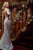 Christmas and New Year celebration. Charming young woman in luxurious evening dress and with beautif poster